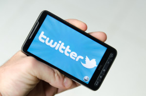 Hand holding a smarthphone showing twitter application